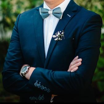 L'attraente sposo in abito con farfallino e fiore all'occhiello o asola sulla giacca