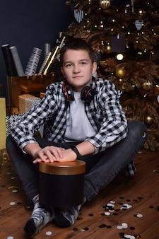 Ragazzo attraente adolescente seduto sul pavimento del soggiorno di natale e con in mano una scatola