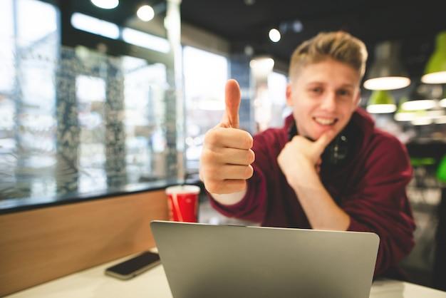 Ragazzo attraente con un computer portatile nella caffetteria mostra un pollice in alto