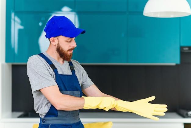 Ragazzo attraente con barba ben curata dal servizio di pulizia che indossa guanti di gomma protettivi per pulire la cucina domestica