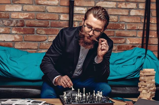 Attraente bell'uomo con occhiali, barba e baffi, seduto sul divano e gioca a scacchi. sul tavolo ci sono riviste, giochi da tavolo. concetto di giochi da tavolo
