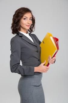 Attraente donna d'affari fiduciosa riccia felice sorridente in costume grigio che tiene raccoglitori colorati con documenti
