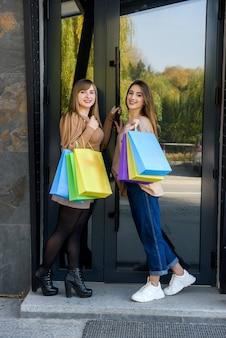 Attraenti clienti felici con pacchetti dopo lo shopping in posa all'aperto