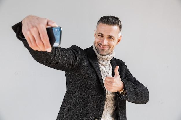 Attraente uomo felice che indossa un cappotto in piedi isolato su un muro grigio, facendo un selfie, dando i pollici in su