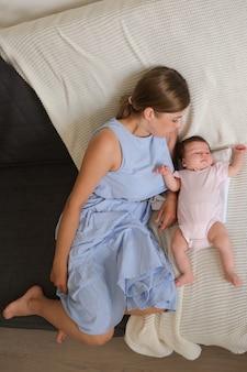 Madre felice attraente che si trova con la piccola neonata sullo strato. vista dall'alto. famiglia felice. a casa. amore. dolce. tenerezza. foto di alta qualità