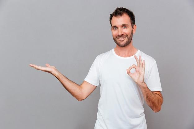 Attraente giovane casual sorridente felice in maglietta bianca che tiene copyspace sul palmo e mostra un gesto ok su sfondo grigio