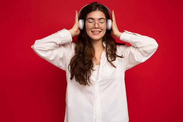 Attraente giovane donna bruna sorridente felice che indossa una camicia bianca e occhiali ottici
