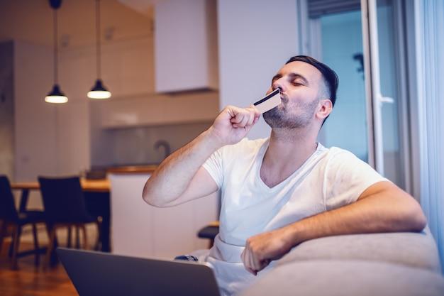 Uomo caucasico non rasato felice attraente in pigiama che si siede sul sofà in salone con il computer portatile in grembo e che bacia la sua carta di credito.