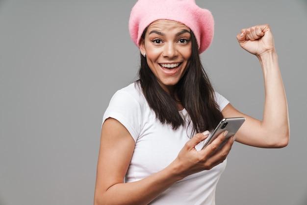 Attraente giovane donna bruna felice che indossa un berretto in piedi isolato su un muro grigio, tenendo il telefono cellulare, celebrando il successo