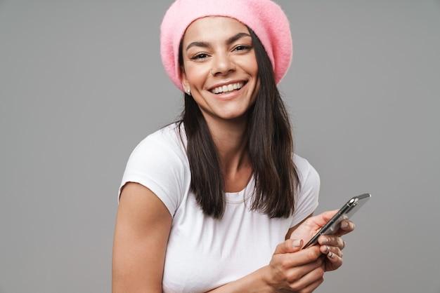 Attraente giovane donna bruna felice che indossa un berretto in piedi isolato su un muro grigio, con in mano un telefono cellulare