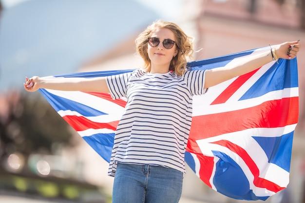 Attraente ragazza felice con la bandiera della gran bretagna.