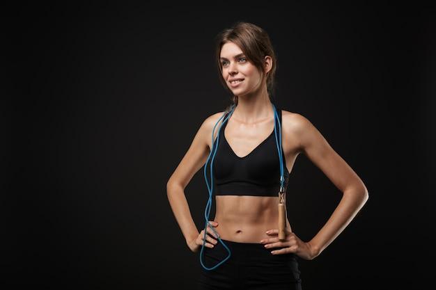 Attraente felice giovane donna in buona salute che indossa reggiseno sportivo e pantaloncini isolati su sfondo nero, che si esercita con la corda per saltare
