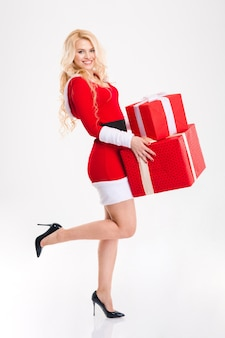 Attraente giovane donna felice in costume rosso di babbo natale che tiene regali su sfondo bianco