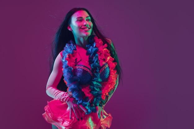 Modello castana hawaiano attraente sulla parete viola dello studio alla luce al neon