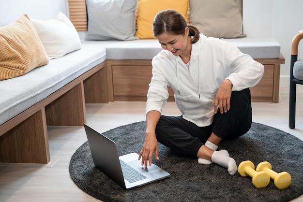 Attraente e sana giovane donna asiatica facendo esercizio a casa durante l'allenamento in abiti comodi su una stuoia nel suo salotto, concetto di stile di vita sano.