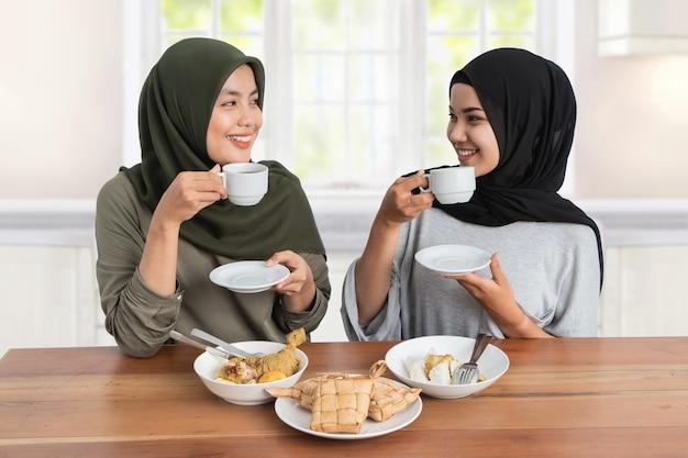 Attraente donna hijab che fa colazione mangiando un po 'di ketupat o un piatto di torta di riso