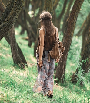 Attraente ragazza hippie che cammina tra gli alberi della foresta. il concetto di unità con la natura