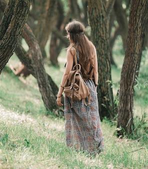 Attraente ragazza hippie che cammina attraverso la foresta