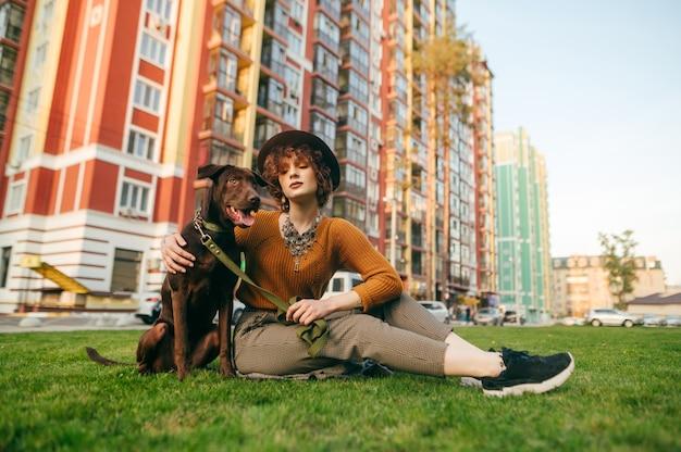 Attraente ragazza hipster in cappello e vestiti alla moda si siede sul prato in cortile e abbraccia un cucciolo