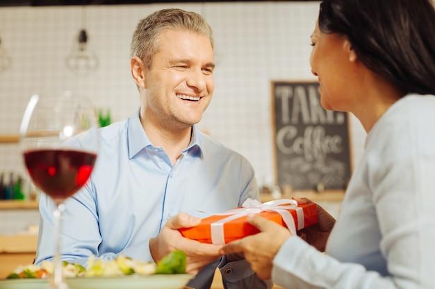 Attraente uomo ben costruito ispirato che sorride e fa un regalo alla sua bella amata donna felice mentre cena romantica