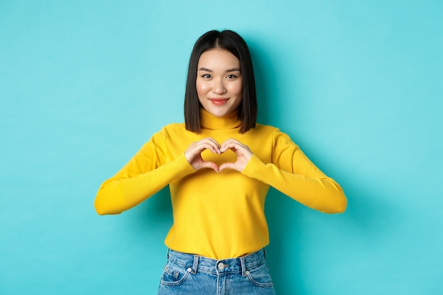 Attraente ragazza giapponese in maglione giallo, che mostra il gesto del cuore e dice ti amo, guardando sinceramente la telecamera, in piedi su sfondo blu
