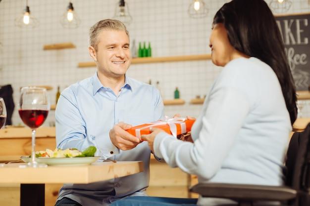 Uomo biondo gioioso attraente che sorride e che dà un regalo alla sua bella donna disabile allegra mentre cena