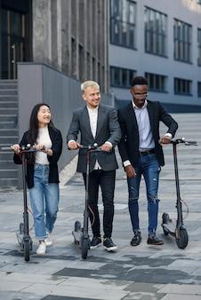 Colleghi di ufficio multirazziali gioiosi attraenti cavalcando scooter elettrici vicino a un bellissimo edificio architettonico.