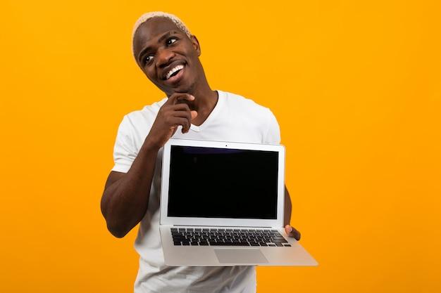 Computer portatile americano sorridente allegro attraente della tenuta dell'uomo con il modello e sognare sul fondo giallo