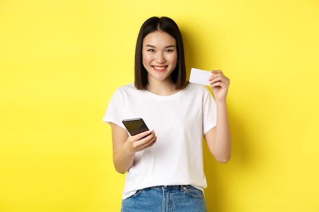 Attraente donna coreana che paga online con lo smartphone, mostrando la carta di credito in plastica e sorridente, in piedi su sfondo giallo.
