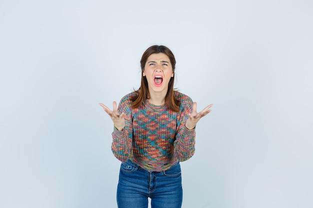 Signora attraente che fa gesto di domanda in maglione, jeans e sembra furiosa. vista frontale.