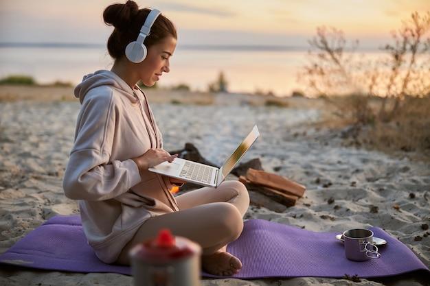 Attraente signora in felpa che usa il taccuino e sorride mentre è seduta sul tappetino da yoga sulla spiaggia