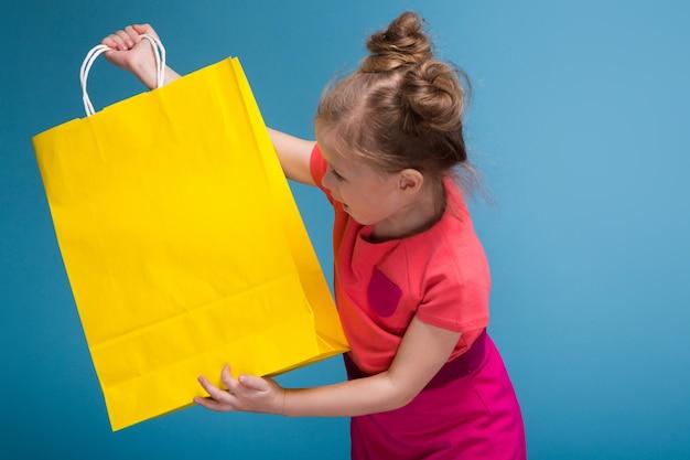 La piccola ragazza sveglia attraente in vestito rosa tiene il sacco di carta giallo