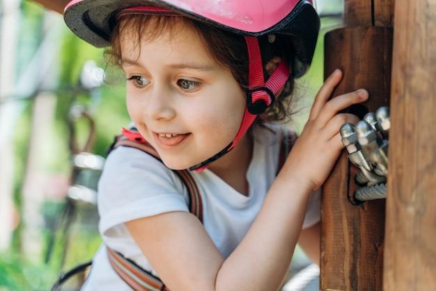 Bambina attraente in un casco protettivo sulla funivia. la ragazza trascorre attivamente del tempo all'aperto