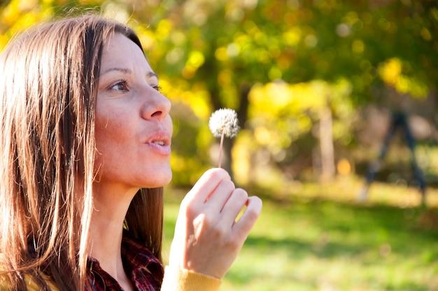 Attraente donna dai capelli lunghi nel parco che soffia un ...
