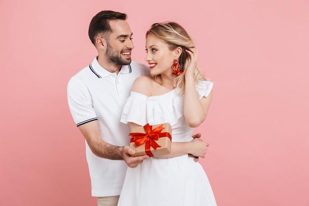 Attraente e adorabile giovane coppia innamorata in piedi insieme isolata sul rosa, facendo regali, celebrando l'evento