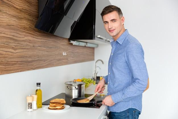 Attraente maschio in camicia blu in piedi e prepara frittelle in cucina