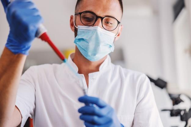Assistente di laboratorio maschio attraente con guanti di gomma e maschera facciale che tiene la provetta con sangue e fa ricerca per la cura per il virus corona.
