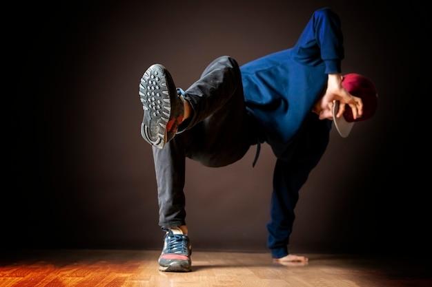 Attraente ballerino di strada maschio esegue il gioco di gambe di break dance b