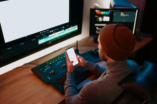Attraente editor video maschio lavora con filmati o video sul suo personal computer e si diverte a comunicare sul suo smartphone. lavora in creative office studio oa casa. luci al neon