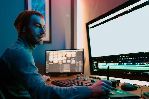 Attraente editor video maschile funziona con filmati o video sul suo personal computer, lavora in creative office studio oa casa. luci al neon