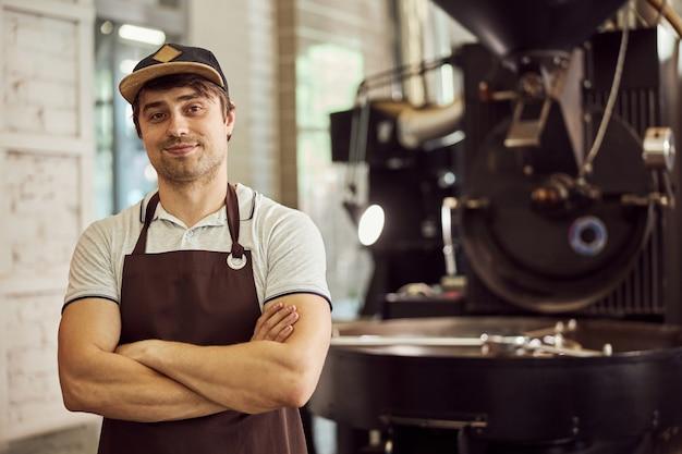 Attraente lavoratore di sesso maschile in grembiule che guarda l'obbiettivo e sorridente. attrezzatura professionale per la torrefazione dei chicchi di caffè su sfondo sfocato