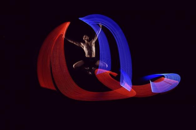 Balletto attraente uomo che balla con effetto di luci incandescente