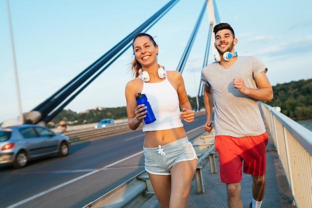 Uomo attraente e bella donna che fanno jogging insieme sul ponte
