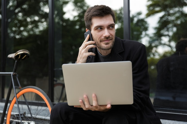 Attraente uomo vestito di cappotto seduto per strada, utilizzando il computer portatile, parlando al telefono cellulare