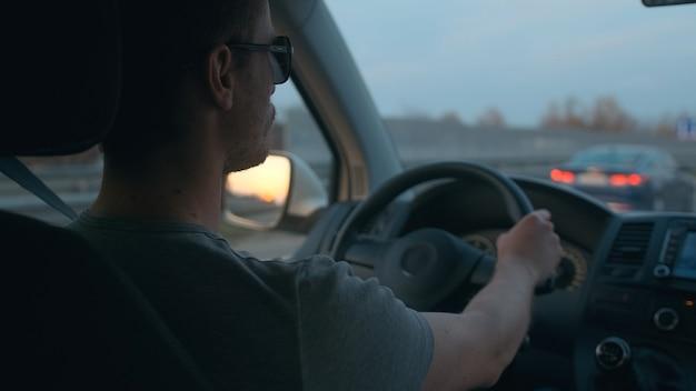 L'uomo attraente che guida l'auto lungo l'autostrada urbana