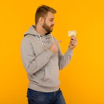 L'uomo attraente in una felpa con cappuccio grigia punta il dito contro la carta di credito che tiene in mano su uno sfondo giallo - immagine