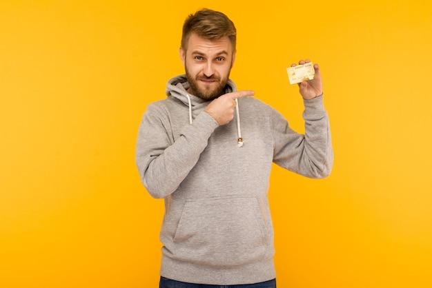 L'uomo attraente in una felpa con cappuccio grigia punta il dito contro la carta di credito che tiene in mano su uno sfondo giallo