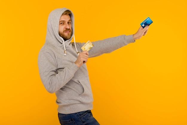 L'uomo attraente in una felpa grigia tiene due carte di credito nelle sue mani su uno spazio giallo