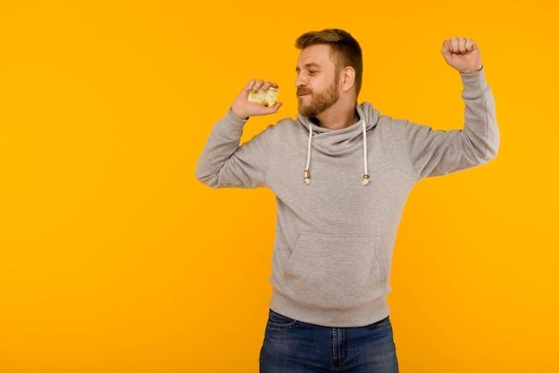 Uomo attraente in una felpa grigia balla con gioia con una carta di credito in mano su uno sfondo giallo - immagine