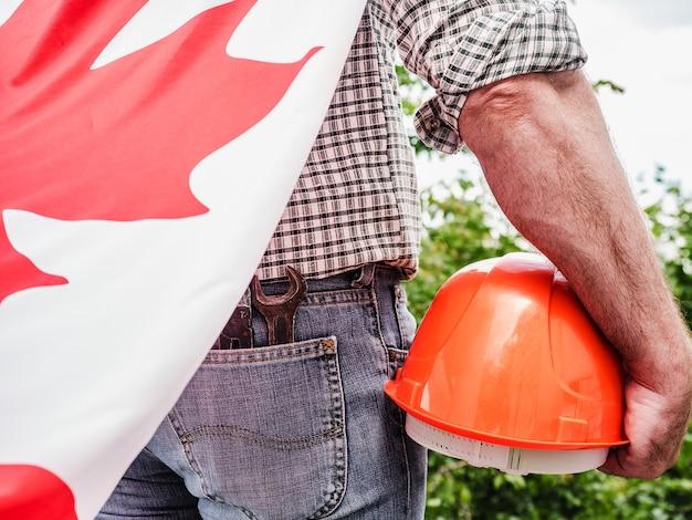 Uomo attraente che tiene una bandiera canadese su sfondo blu cielo in una giornata limpida e soleggiata. vista dal retro, primo piano. concetto di festa nazionale